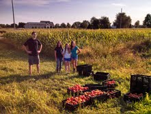 Jeremy Shue, Director of  the Goshen Garden, with volunteers stand proudly behind vegetables they just harvested.